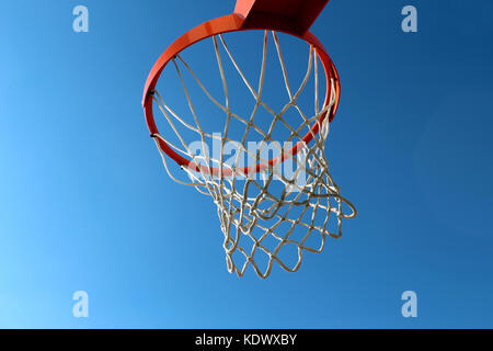 Orange basketball rim (hoop) and white net against blue sky seen from below - Stock Photo