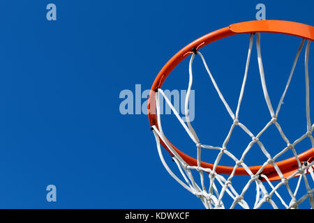 Detail of an orange basketball rim (hoop) and white net against blue sky seen from below - Stock Photo