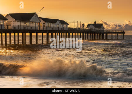 On a stormy morning in early August the sky turns orange as the sun rises behind the Pier in the popular Suffolk - Stock Photo