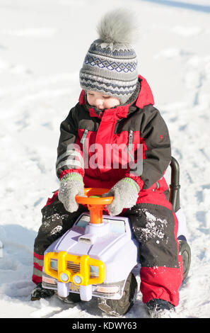 Little boy in red outfit playing happily over the snow - Stock Photo