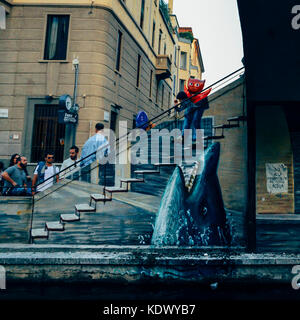 Surreal graffiti in Milan, Italy's Bohemian Navigli district - Stock Photo