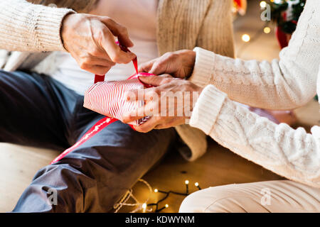 Unrecognizable senior couple in white woolen sweaters sitting on the floor, wrapping Christmas gifts together. - Stock Photo