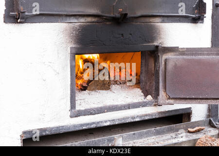white wood oven with the door open iron and wood burning - Stock Photo
