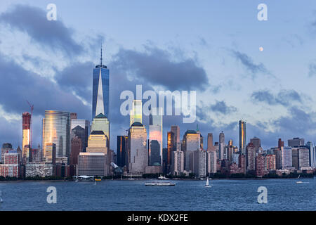 Lower Manhattan Skyline and moon rising at blue hour, NYC, USA - Stock Photo