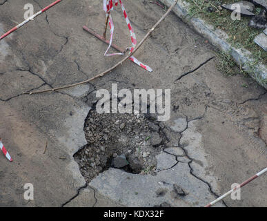A hole in the asphalt in the courtyard of a residential area. Damaged road - Stock Photo