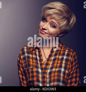 Funny grimacing woman with short blond hair style posing in yellow Halloween shirt on grey background. Closeup toned - Stock Photo