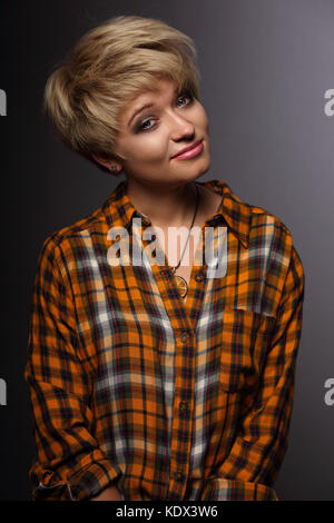 Funny grimacing woman with short blond hair style posing in yellow Halloween shirt on grey background. Closeup portrait - Stock Photo