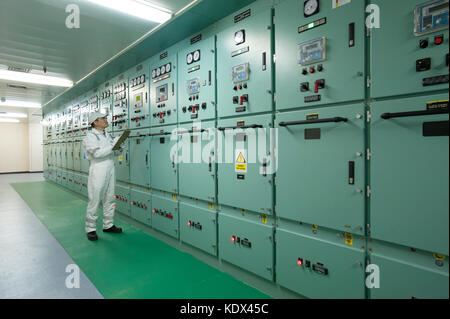 Ship's engineering officer in engine control room - Stock Photo