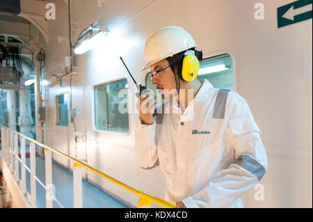 Ship's engineering officer in engine room talking on VHF radio - Stock Photo