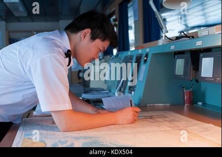 Navigation officer on a merchant ship plotting a course - Stock Photo