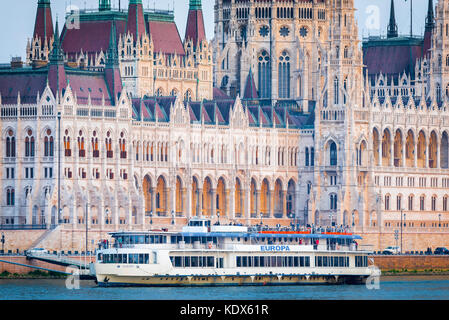 Danube cruise, view of a cruise ship on the River Danube sailing past the  Hungarian Parliament Building, Budapest. - Stock Photo
