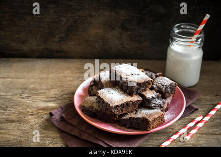 Brownies for Christmas and winter holidays. Homemade chocolate fudge brownies with milk on rustic wooden table. - Stock Photo