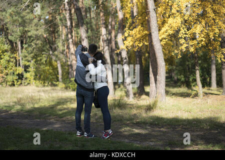A loving young couple doing selfie in the park - Stock Photo
