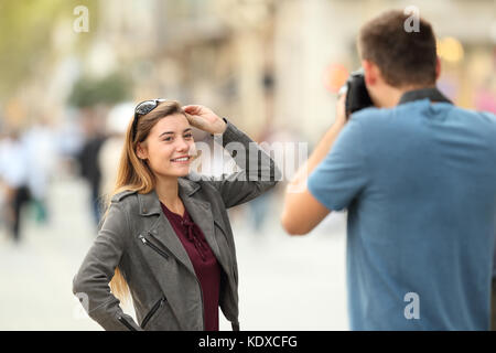 Photographer photographing to a fashion model on the street - Stock Photo