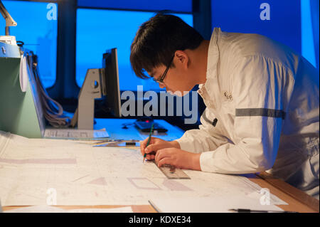 Navigation officer on a merchant ship plotting a course at night - Stock Photo