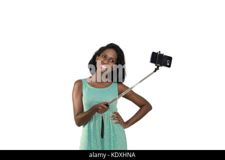 Woman taking selfie with stick - Stock Photo