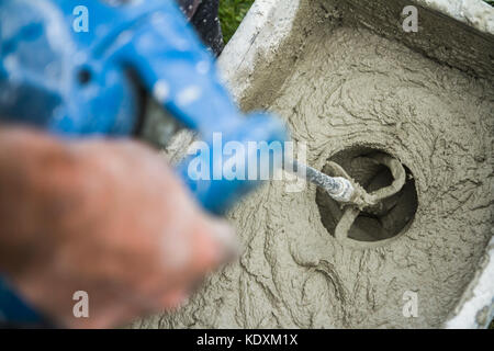 Worker mixing plaster with a drill in a bucket - Stock Photo