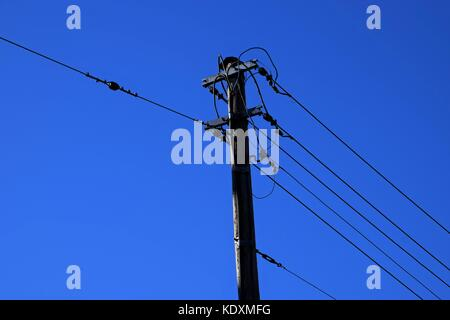 high power pole in the Country, power cable in autumn with colorful blue sky - Stock Photo