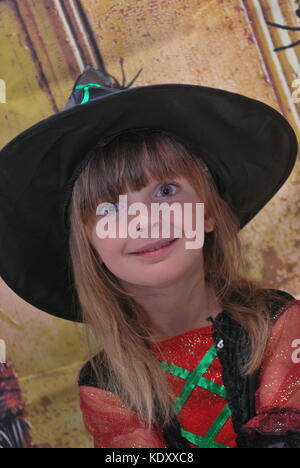 Little girl wearing a witch costume who is very excited for Halloween - Stock Photo