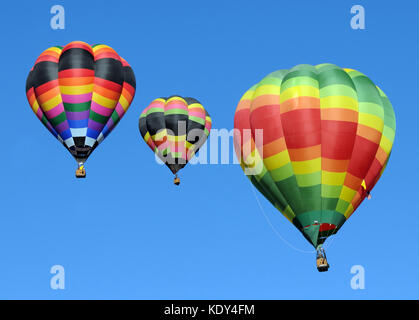 Three colorful hot air balloons against blue sky - Stock Photo