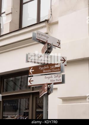 Signpost with directions for tourists and locals in downtown Tbilisi Georgia in two alphabets - Stock Photo