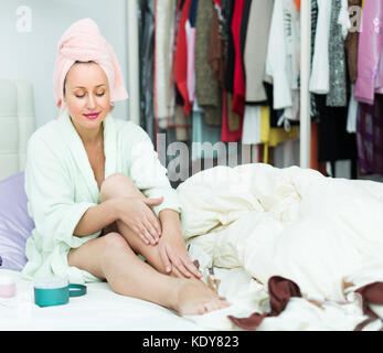 Happy woman sitting on bed and applying cream on her legs skin - Stock Photo