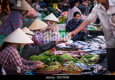 Women in rice hats setting fresh vegetables and fish in Dong Ba Market - Stock Photo