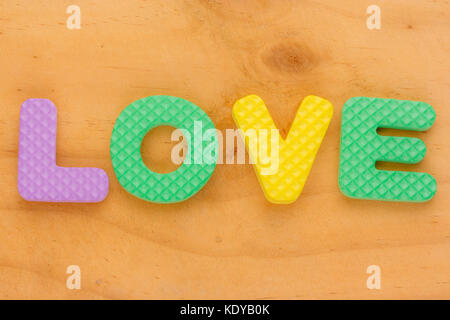 foam letter forming word love on wood background - Stock Photo