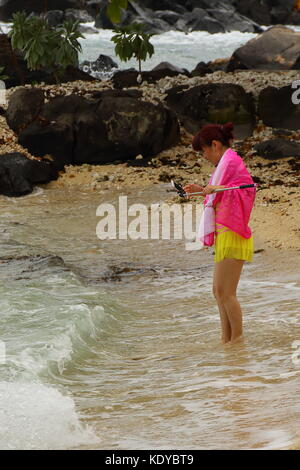 Balaclava, Mauritius - an unidentified tourist takes a selfie on the beach at Turtle Bay in portrait format - Stock Photo