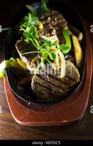 Grilled beef steak served with pan-fried vegetables and topped with coriander. The dish is an example of fusion - Stock Photo