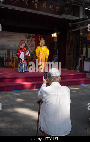 guangzhou,china - Aug,16,2017: Old man watching contonese opera show with moblie. - Stock Photo