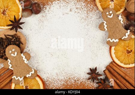 Holiday baking themed frame with gingerbread men, nuts and spices against a powdered sugar background - Stock Photo