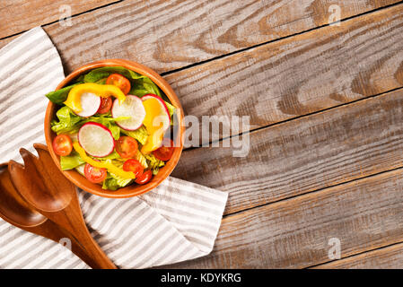 Fresh healthy salad with lettuce,tomatoes,pepper, radish on  wooden background top view with cotton napkin.Food - Stock Photo