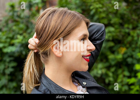 Profile view of a beautiful young woman holding her hair in a ponytail outdoor - Stock Photo
