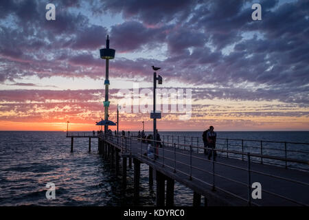 People enjoy a gorgeous sunset at the seaside on Adelaide's Brighton jetty on a balmy summer evening. - Stock Photo
