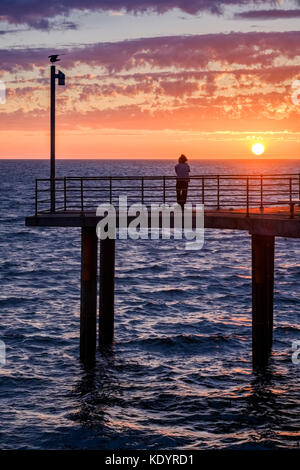 A lone person enjoys a gorgeous sunset at the seaside on Adelaide's Brighton jetty on a balmy summer evening. - Stock Photo