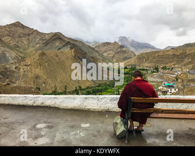 Young monk sitting overlooking the Himalayas - Stock Photo
