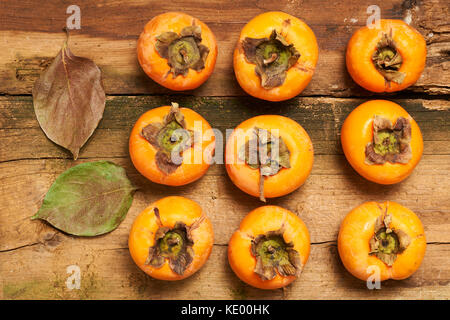 Six fresh persimmons and two leaves on an old table - Stock Photo