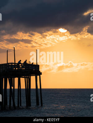 Fisherman try their luck shortly after sunrise at the Avon fishing pier on Hatteras Island, North Carolina. - Stock Photo