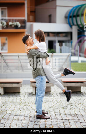 Euphoric young couple meeting and hugging on the street. Smiling couple in love standing on the street - Stock Photo