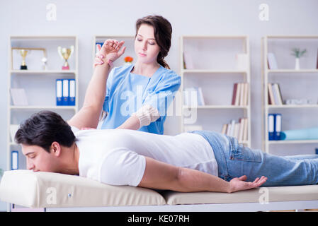 Female chiropractor doctor massaging male patient - Stock Photo