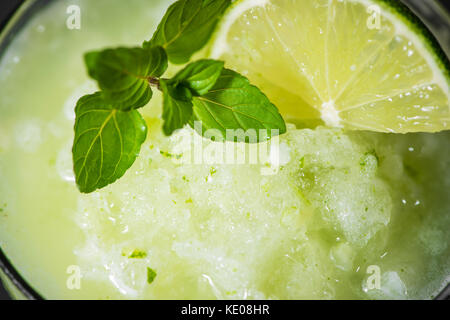 Cocktail juice with lime, mint and ice. Bar drink accessories on black table background. - Stock Photo