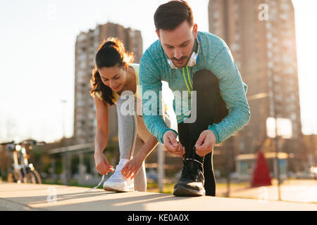 Runners tying running shoes and getting ready to run - Stock Photo