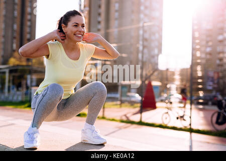 Young woman doing squats in urban area - Stock Photo