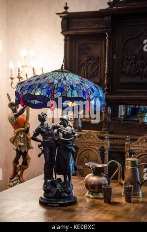 Tiffany Style Blue Vintage Table Lamp with statuette 'Unity' as a pole in candles light - Stock Photo