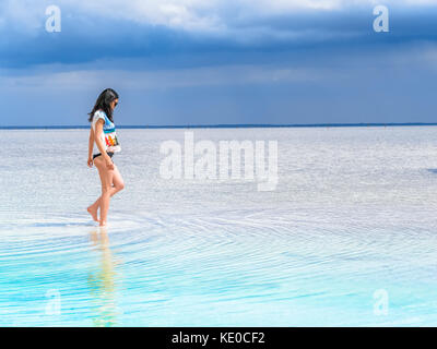 A girl walks along the surface of a salt lake at a spa resort. Young woman on the beach with white sand and beautiful - Stock Photo