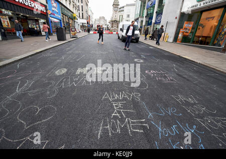 Brighton, UK. 17th Oct, 2017. Members of the public have turned a Brighton Street into a blank canvas for artwork and graffiti while it is being repaired . North Street in the city centre is having essential improvement work carried out by Southern Water and while it is empty public have started to leave chalk messages and artwork on the newly laid tarmac Credit: Simon Dack/Alamy Live News Stock Photo