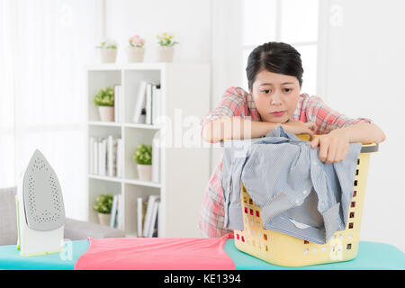 attractive beauty housewife leaning on clothing basket feeling tired about ironing sort out family clothes and daze - Stock Photo