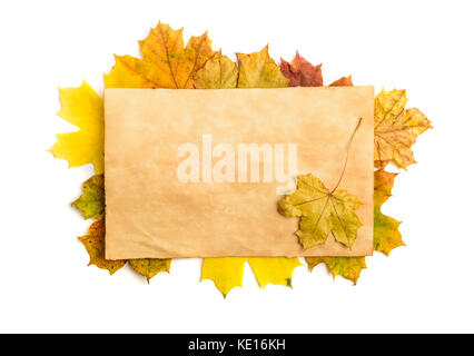 Old grunge paper page over fall leaves isolated on white - Stock Photo