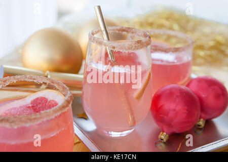 Pink bubbly cocktail and festive christmas decorations - Stock Photo